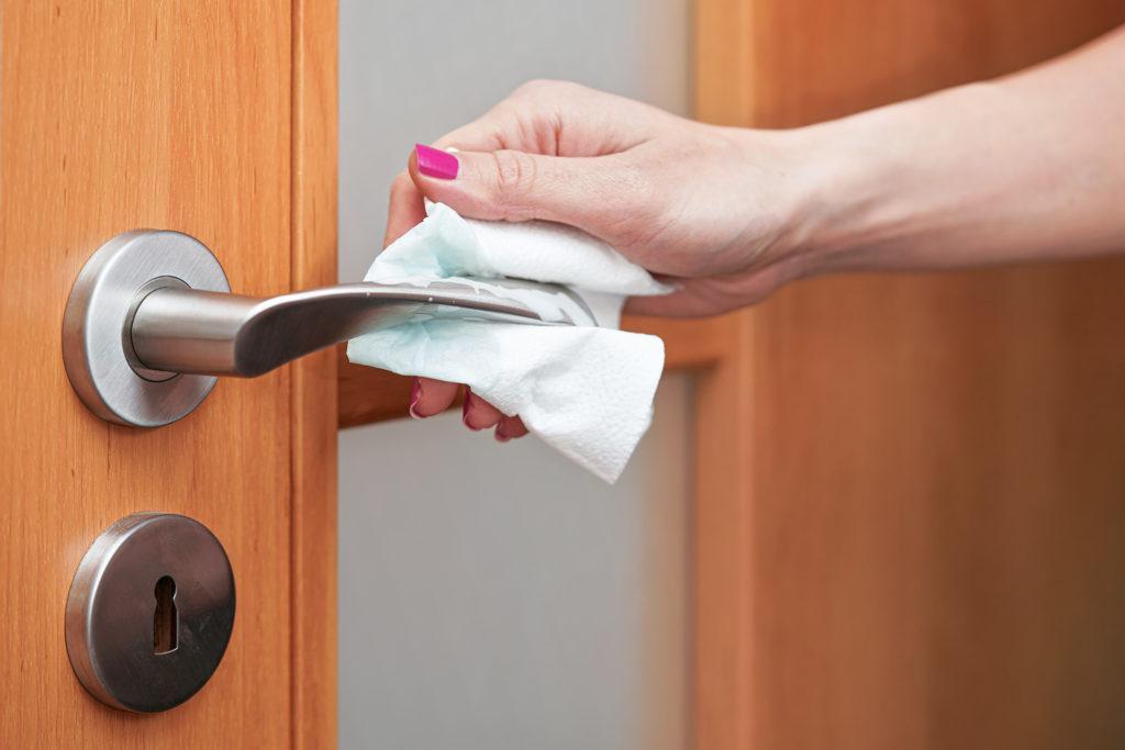 Foto von einem Türgriff der von einer Frauenhand mit einem Tuch desinfiziert wird.